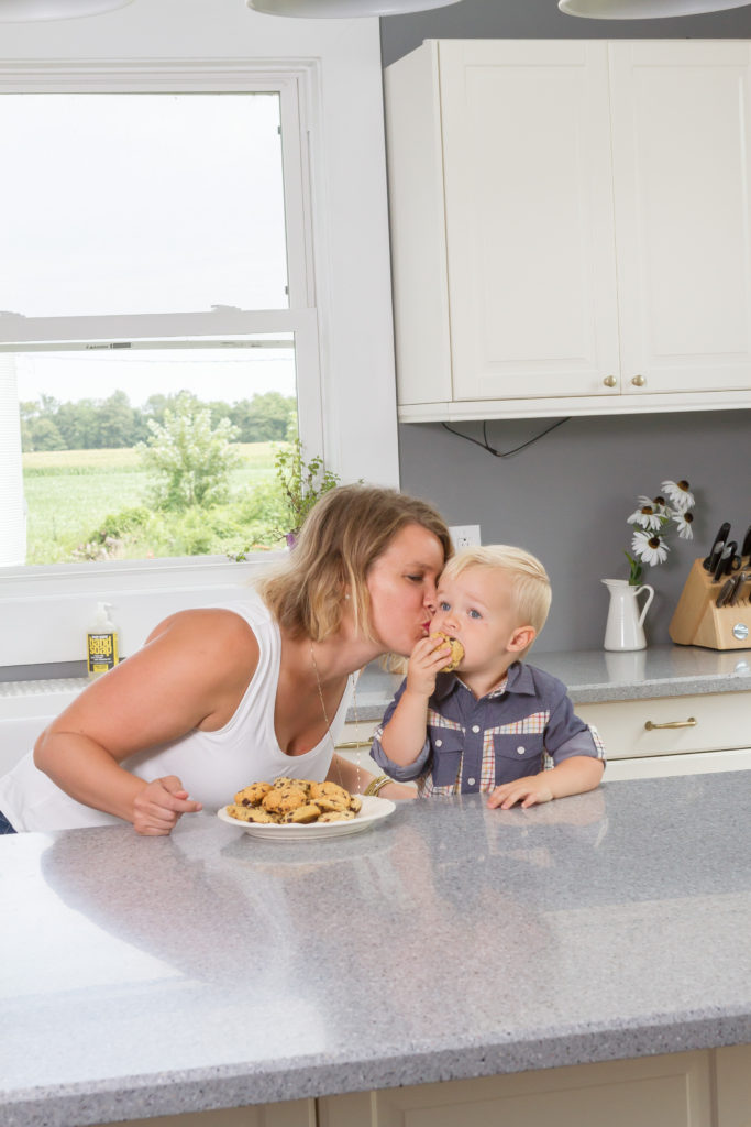 Mom kissing son on the cheek in kitchen