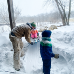 dad and kids building a snow fort
