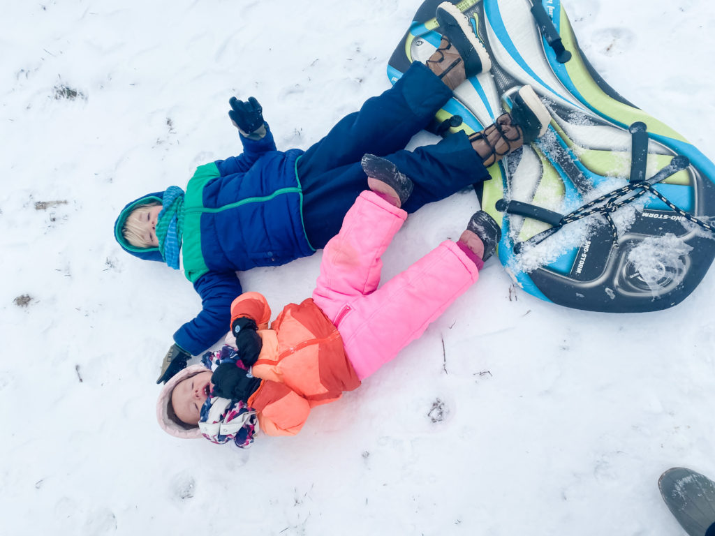 Kids falling over in snow, snow suits, tired of the snow, kids sledding in snow | 1000 Hours Adventure - February Recap | IgniteNourishThrive.com